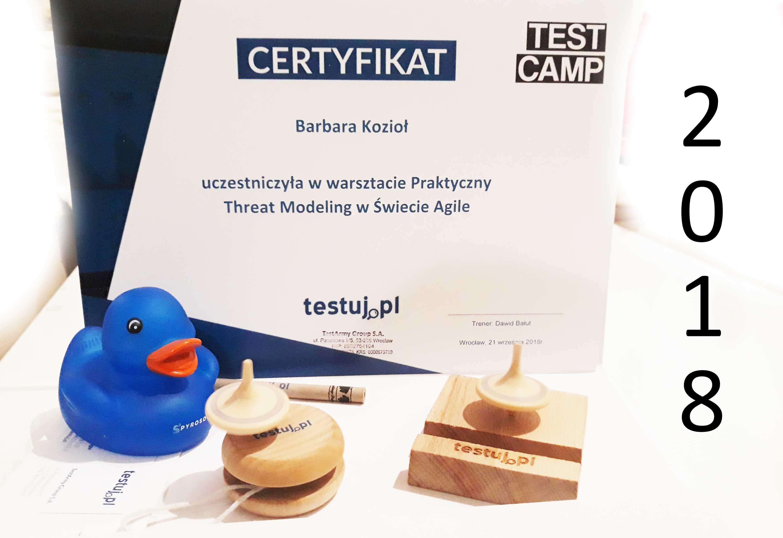 Certyfikat uczestwnictwa w warsztatach Praktyczny Threat Modeling wśród gadżetów z konferencji.